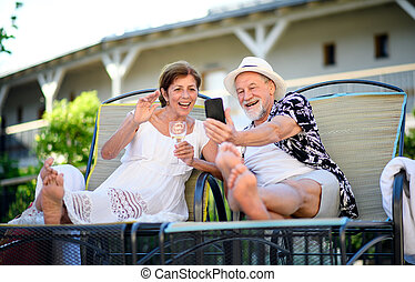 Senior couple with smartphone outdoors on holiday, video call concept.