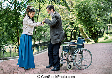 Senior disabled man trying to stand up from the wheelchair, with the help of his pretty young granddaughter with long dreadlock hair, smiling and enjoying good health results after desease