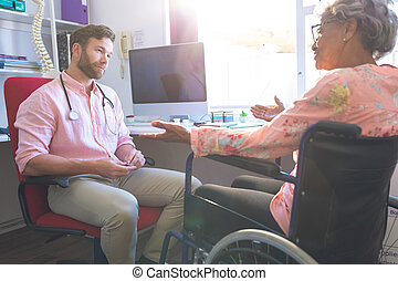 Senior female patient talking with doctor in clinic