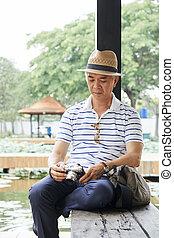 Senior man checking photos on camera