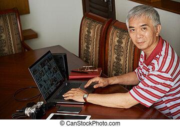 Senior man editing photos on laptop