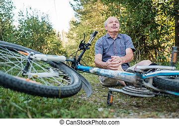 Senior man has a pain after he fell from his bike.