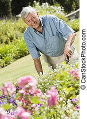 Senior man in a flower garden