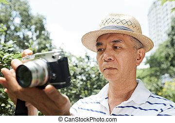 Senior man looking at screen of camera