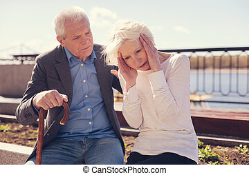 Senior man looking worriedly at his ill wife