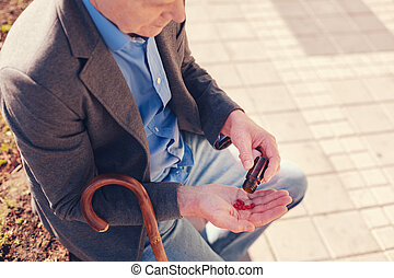 Senior man pouring red capsules on his hand