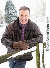 Senior Man Standing Outside In Snowy Landscape