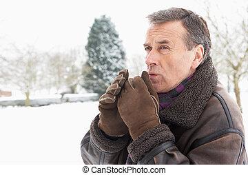 Senior Man Standing Outside In Snowy Landscape Warming Hands