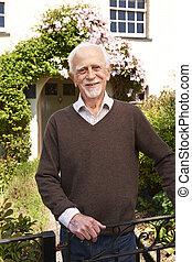 Senior Man Standing Outside Pretty Cottage