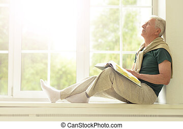 Senior man with book at home