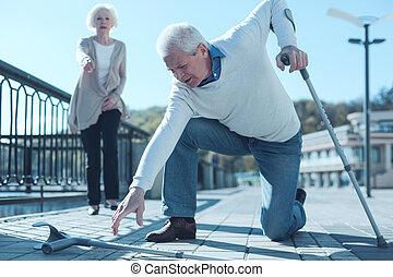 Senior man with crutches hitting the ground
