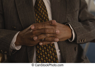 Senior man with hands clasped at nursing home