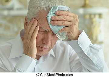 Senior man with headache at home