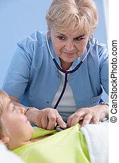 Senior pediatrician examining boy