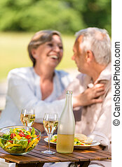 Senior wife and husband dining outdoors