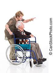 senior woman behind disabled husband and pointing