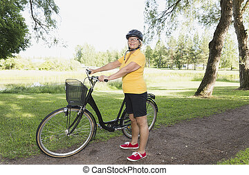 Senior woman bicycling in a park at sunny afternoon