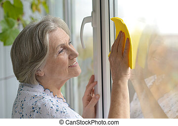 Senior woman cleaning window at home