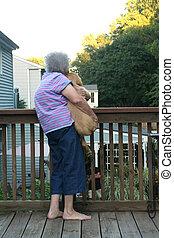 Senior Woman Holding Puppy Vertical
