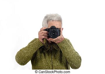 Senior woman shooting with a camera reflex