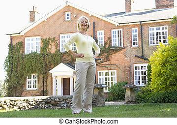 Senior Woman Standing Outside House