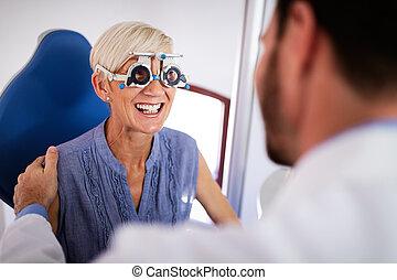 Senior woman taking an eyesight test examination at an optician clinic