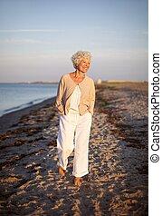 Senior woman walking on the beach