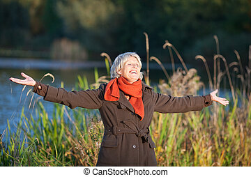 Senior Woman With Arms Outstretched Enjoying Sunlight