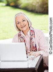 Senior Woman With Laptop At Nursing Home Porch