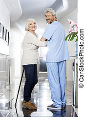 Senior Woman With Stick And Physiotherapist Standing In Rehab Ce