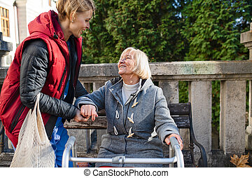 Senior woman with walking frame and caregiver outdoors sitting in park, helping to stand up.