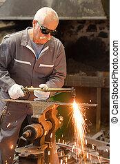 senior worker soldering outdoors