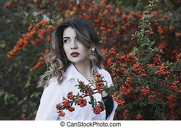 Sensual young woman in white shirt with makeup and curly hair posing near bush with orange berries in the park.
