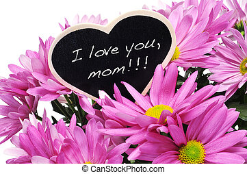 sentence I love you, mom written with chalk on a heart-shaped blackboard on a bouquet of pink chrysanthemums