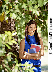Sequence of students portrait at school, happy young woman smiling with college textbooks in park leaning on tree