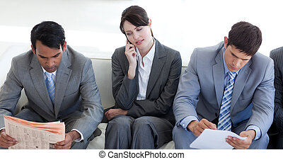 Serious Business people sitting and waiting for a job interview