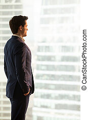 Serious businessman lost in thoughts standing looking at city bu