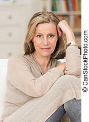 Serious thoughtful middle-aged woman sitting with her knees up on a sofa staring directly at the camera