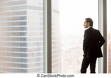 Serious young businessman standing in modern office, looking out