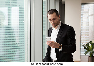 Serious young handsome businessman in modern office looking at c