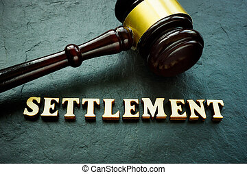 Settlement word from wooden letters and gavel.