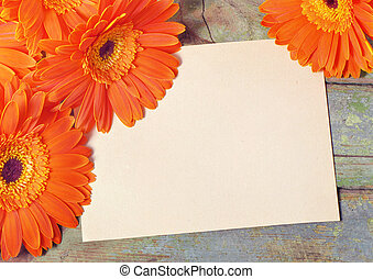 Sheet of paper for notes on a wooden board surrounded by orange flowers