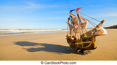 Ship model on summer sunny beach