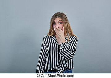 Shocked blonde woman looking at camera, covered mouth with hand