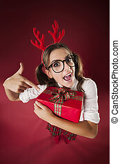 Shocked nerdy woman pointing at christmas gift
