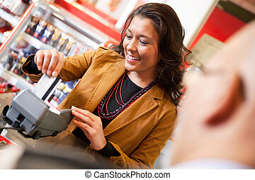 Shop assistant smiling while swiping credit card