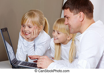 Portrait of father showing something at laptop to their daughters