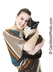 A beautiful Snowshoe Lynx Point Siamese cat being hugged by her female owner. Shot on white background.