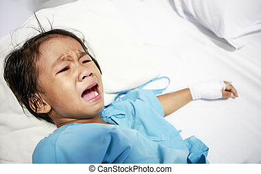 Sick little girl crying in hospital bed
