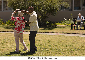 senior couple dancing together in garden